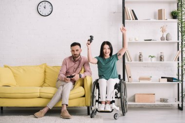 KYIV, UKRAINE - JULY 10, 2019: Excited disabled woman showing yes gesture while playing video game with boyfriend at home. stock vector