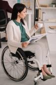 Fotografie schöne behinderte Geschäftsfrau, während sie am Arbeitsplatz im Rollstuhl sitzt