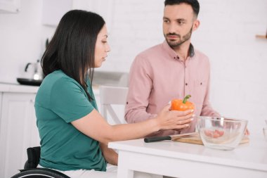 young disabled woman holding bell pepper while talking to boyfriend in kitchen