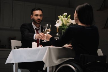 back view of disabled young woman clinking glasses of red wine with handsome boyfriend during romantic dinner