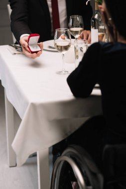 partial view of boyfriend making wedding proposal to disabled young woman while having romantic dinner