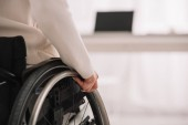 Behinderte Geschäftsfrau sitzt im Rollstuhl neben Schreibtisch mit Laptop