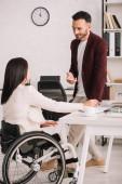 usmívající se podnikatel, který drží smartphone a stojí poblíž zdravotně postižené ženy v kanceláři