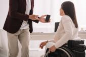 Ausgeschnittene Ansicht eines Managers, der behinderten Geschäftsfrau Smartphone mit leerem Bildschirm zeigt