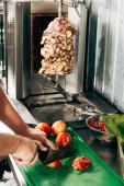 částečný pohled na kuchařský porcování rajčat v kuchyni