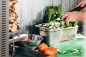 ořezávaná zobrazení kuchařka s nožem u stolu s řezanou zeleninou