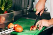 oříznutý pohled na kuchařku na sekání rajčat