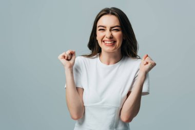 excited beautiful girl in white t-shirt showing yes gesture isolated on grey