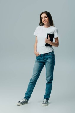 Happy beautiful girl in white t-shirt and jeans with notebook isolated on grey stock vector