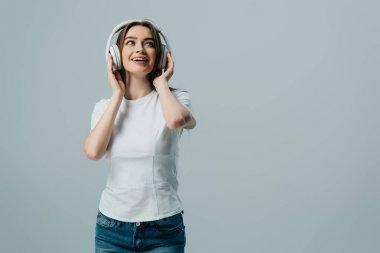 Happy dreamy girl listening music in wireless headphones isolated on grey stock vector