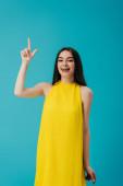 šťastná dívka ve žlutých šatech ukazující prstem nahoru izolovaná na tyrkysové