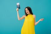 boldog barna nőt sárga ruhában táncoltak útlevél a légi jegyet izolált türkiz