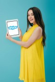 KYIV, UKRAINE - JUNE 6, 2019: smiling beautiful girl in yellow dress showing digital tablet with skype app isolated on turquoise