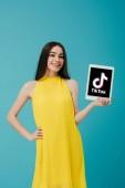 Kyjev, Ukrajina-6. června 2019: usměvavá dívka ve žlutých šatech s rukou na boku ukazující digitální tablet s aplikací izolovanou na tyrkysové