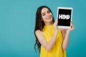 Kyjev, Ukrajina-6. června 2019: šťastná krásná dívka ve žlutých šatech s digitálním tabletem s HBO App, izolovaný na tyrkysové