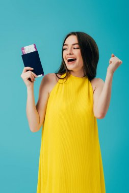 Happy brunette woman in yellow dress holding passport with air ticket and rejoicing isolated on turquoise stock vector