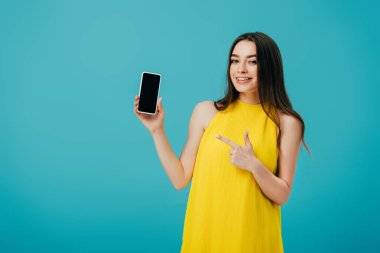 Happy beautiful girl in yellow dress pointing with finger at smartphone with blank screen isolated on turquoise stock vector