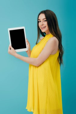 Beautiful brunette girl in yellow dress showing digital tablet with blank screen isolated on turquoise stock vector