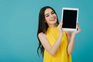 beautiful smiling girl in yellow dress showing digital tablet with blank screen isolated on turquoise