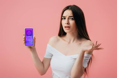 Beautiful confused girl holding smartphone with online shopping app and showing shrug gesture isolated on pink stock vector