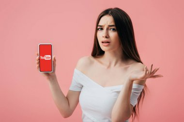 KYIV, UKRAINE - JUNE 6, 2019: beautiful confused girl holding smartphone with youtube app and showing shrug gesture isolated on pink stock vector