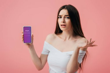 KYIV, UKRAINE - JUNE 6, 2019: beautiful confused girl holding smartphone with Instagram app and showing shrug gesture isolated on pink stock vector