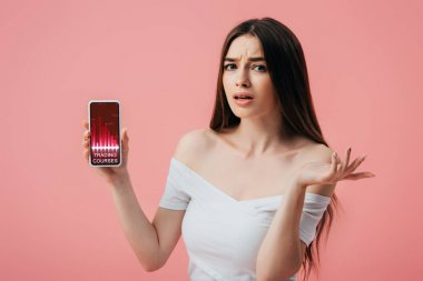 Beautiful confused girl holding smartphone with trading courses app and showing shrug gesture isolated on pink stock vector