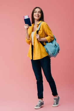 full length view of beautiful smiling girl with backpack holding passport with air ticket isolated on pink