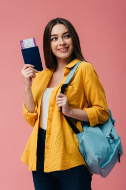 beautiful smiling girl with backpack holding passport with air ticket and looking away isolated on pink