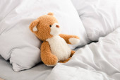 Plüss mackó az ágyban fehér párnákkal és takaróval