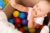 Photo cute child sitting in cardboard box with colorful balls, laughing and raising his hand up