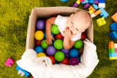 Happy little child sitting in cardboard box with colorful balls and laughing