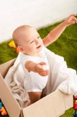 Malé dítě stojící v kartonové krabici s bílou přikrývkou a zvednutím rukou