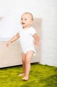 Šťastné malé dítě se usmívá a prochází světlem, s postelí a zeleným kobercem