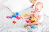 Mezítláb baba fehér ruhában ül az ágyban játékokkal és figyelembe darab építési szájába