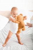 Photo Cute barefoot child in white clothes playing with his teddy bear on the bed