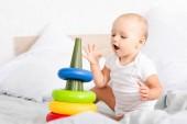 Aranyos kis gyermek fehér ruhában ül az ágyon, és játszik a játék piramis