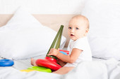 Fotografie Adorable little child in white clothes sitting on bed and holding colorful toy pyramid