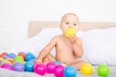 Cute little baby sitting on bed and taking yellow ball into mouth