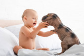 Photo Little child sitting on white bed and holding toy dinosaur with both hands