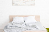 Photo Wooden bed with two white pillows and crumpled blanket in light room