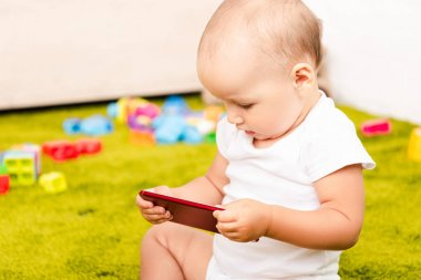 Cute little kid sitting on green floor with toys and holding digital device