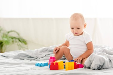 smiling baby in white clothes sitting on bed and looking at toys
