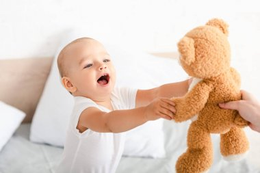 Cute little child in white clothes opening mouth, smiling and raising hands to brown plush bear