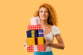 Photo attractive redhead girl holding gift boxes isolated on yellow