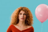 zrzená žena s růžovým balonem izolovaná na modré
