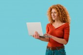 smiling redhead woman using laptop isolated on blue