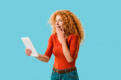 Fotografie surprised woman using digital tablet isolated on blue