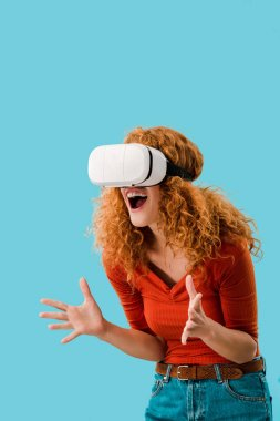 emotional woman screaming in Virtual reality headset isolated on blue