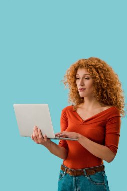 Beautiful redhead woman using laptop isolated on blue stock vector